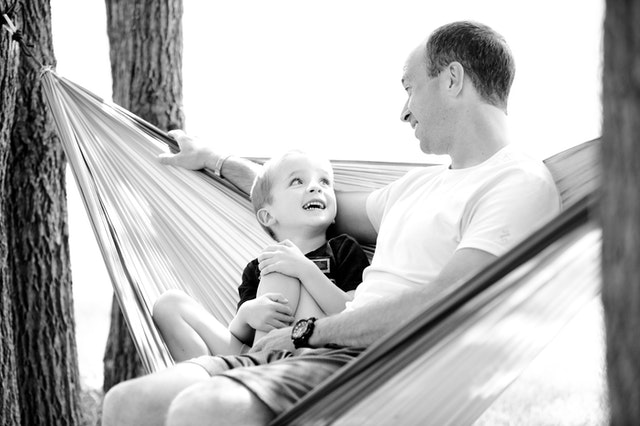 happy father and son hanging out in a hammock