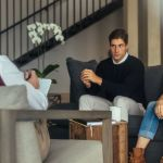 Couple is sitting on sofa and talking to the psychologist